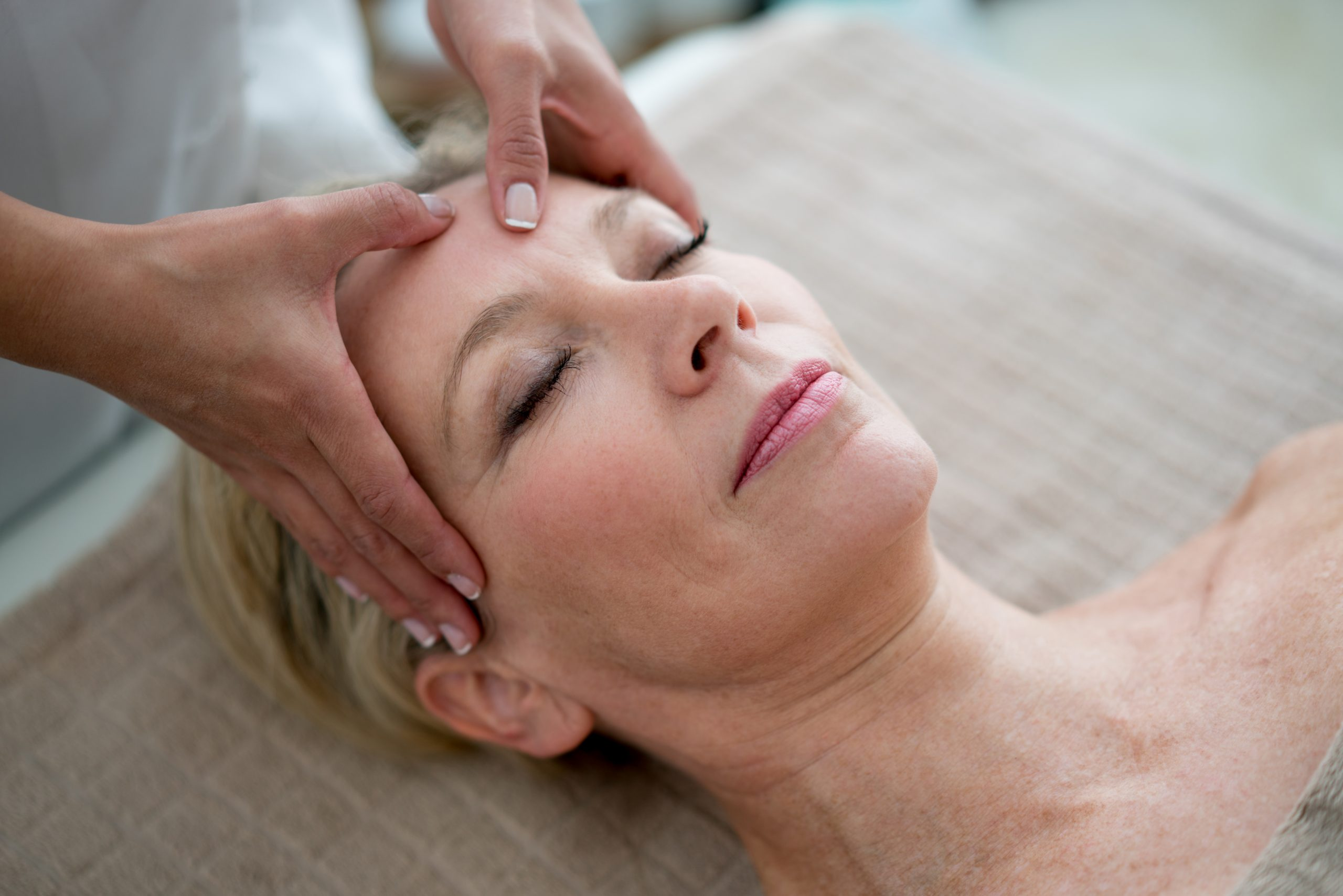 Portrait of an adult woman getting a face massage at the spa - beauty treatment concepts