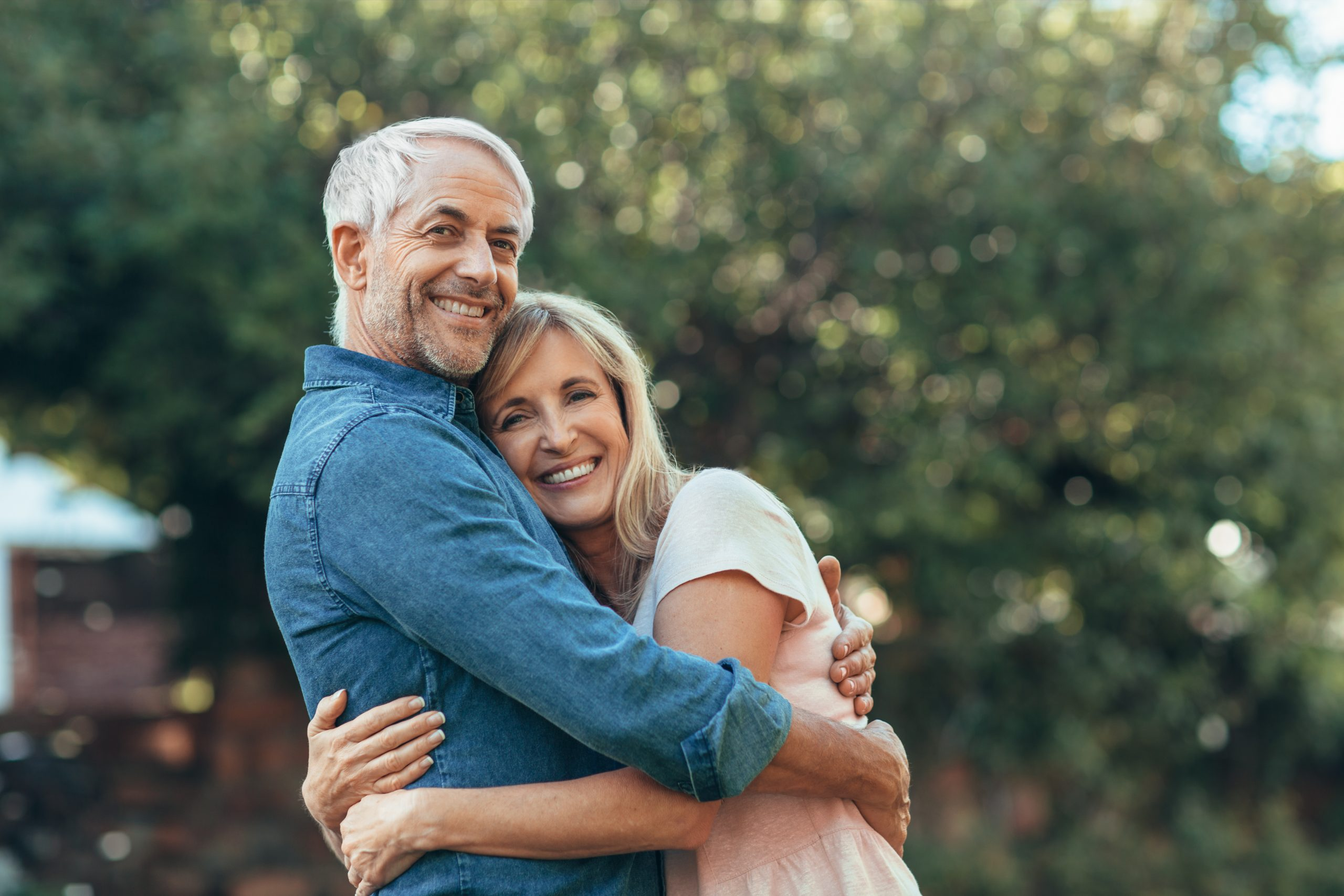 Portrait of a smiling mature couple standing affectionately in each other's arms in their backyard on a sunny day