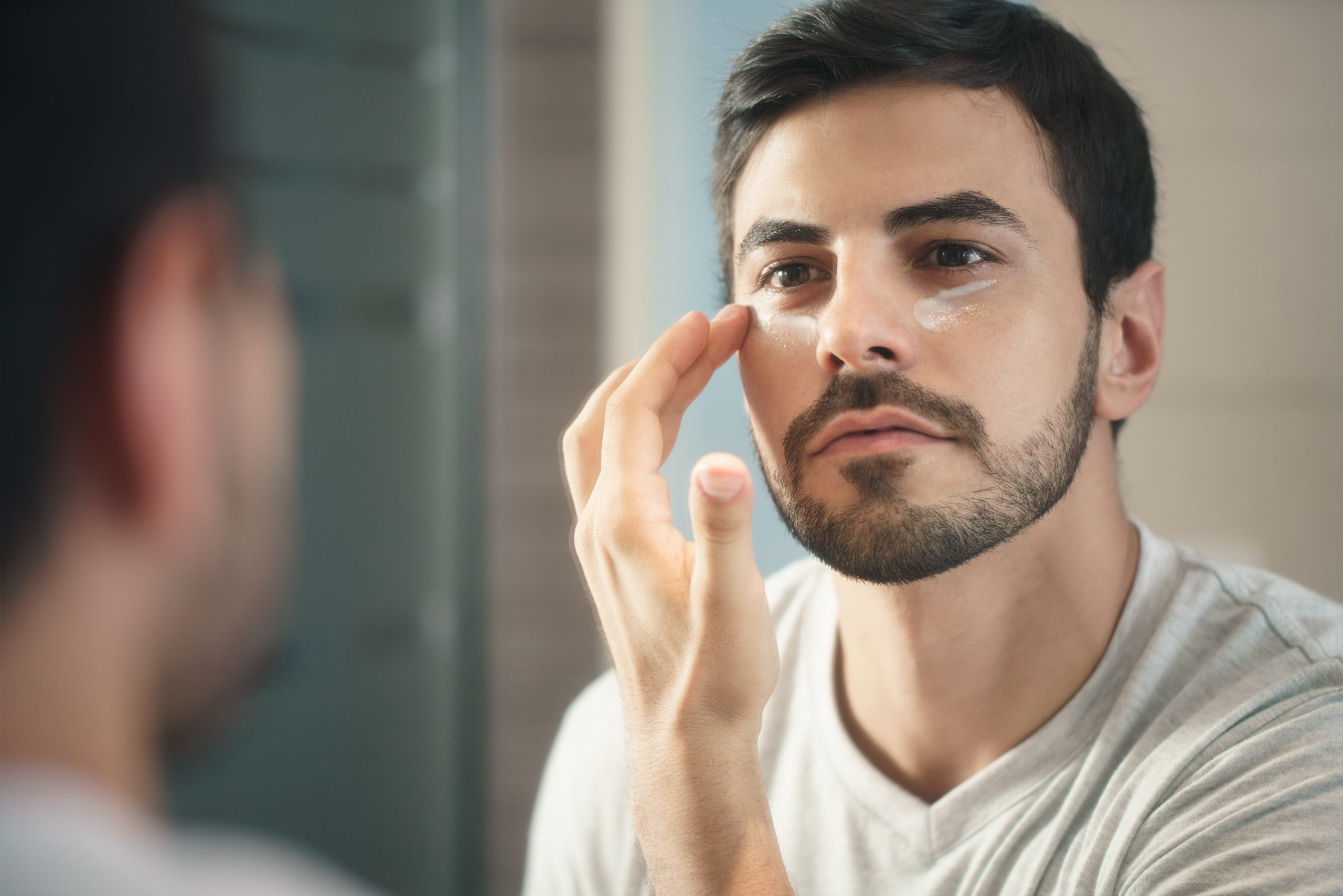 Young man applying skincare cream to face